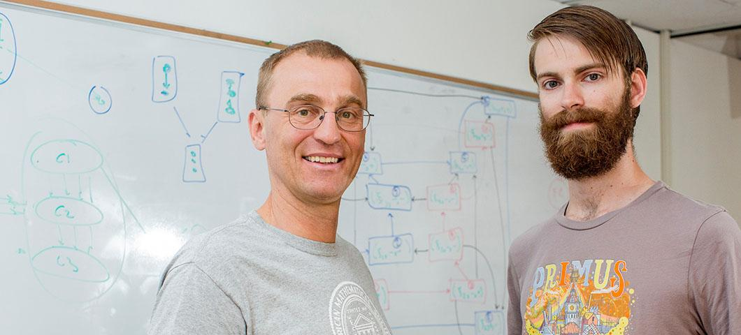 two men standing in front of a whiteboard