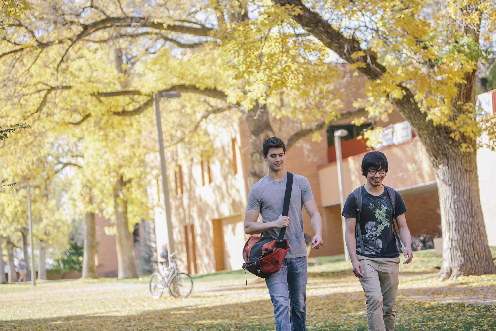 2 students enjoying a fall day outside Wilson Hall.